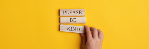 "Yellow background with a hand arranging blocks that read, ""Please be kind."""