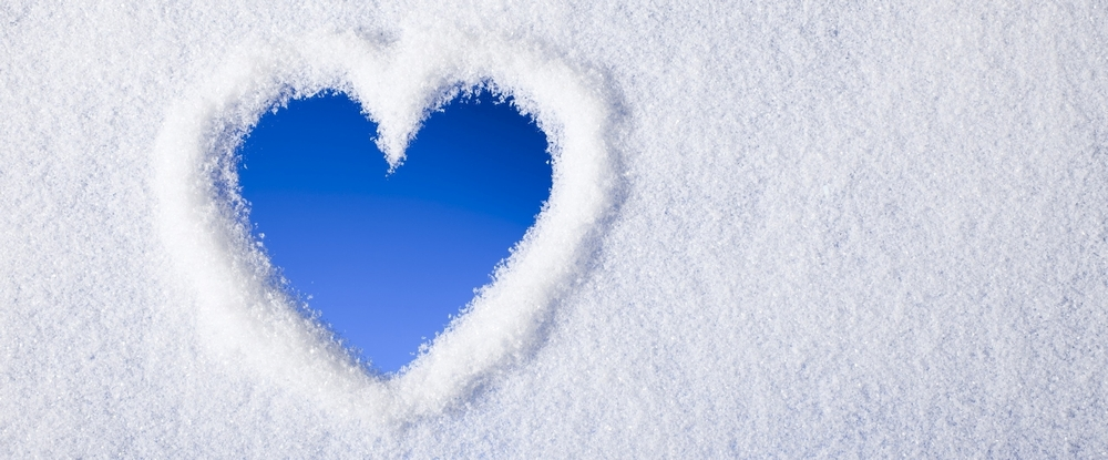 A heart drawn in the snow, showing blue sky beneath.
